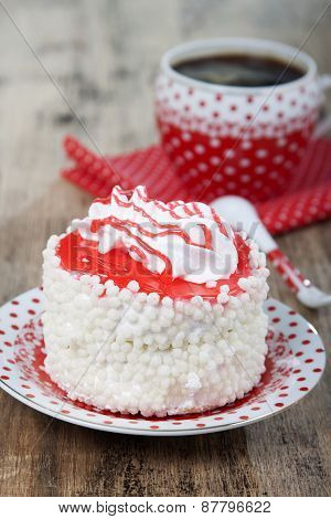 Cake With White Air Protein Cream And Red Confectionery Sprinkles And Red Cup With White Polka Dots