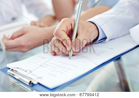 Hand of doctor with pen prescribing medicine