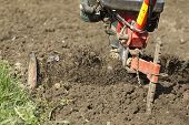stock photo of loam  - Closeup of hand motor plow blade throwing clay - JPG