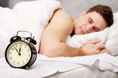 picture of early 20s  - Man lying on the bed with alarm clock - JPG