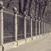stock photo of old stone fence  - Old metal fence around the city park - JPG