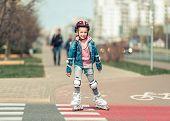 image of bike path  - little cute girl riding on roller skates on the bike path - JPG