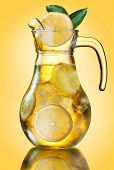 pic of pitcher  - Misted lemonade pitcher with lemon slices and ice cubes decorated with leaves on yellow - JPG