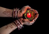 image of diwali lamp  - Woman hands with henna holding candle isolated on black background with clipping path - JPG