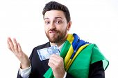 picture of brazilian money  - Brazilian not so happy holding Brazilian money and the flag of Brazil - JPG