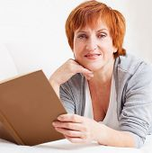 foto of only mature adults  - Adult woman reading book at sofa - JPG