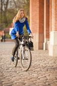 image of cobblestone  - woman cycling on bike on cobblestone in city - JPG