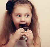 pic of healthy eating girl  - Happy surprising kid girl eating chocolate and looking with long hair style - JPG