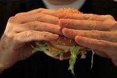 stock photo of hamburger  - Man holding his hamburger close up of hamburger - JPG