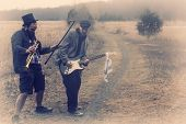 foto of gypsy  - Stylish gypsies play trumpet and electric guitar on a wilderness path in grainy old fashioned grunge photo - JPG