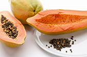 foto of papaya fruit  - Hollowed out half of a raw papaya in longitudinal cross section and its countless peppery seeds on a white plate - JPG