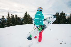 foto of snowboarding  - Rear view of female snowboarder with snowboard in hand standing on top of ski slope looking on ski track - JPG