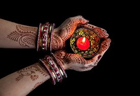 picture of divine  - Woman hands with henna holding candle isolated on black background with clipping path - JPG