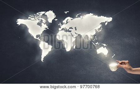 Hand holding coffee cup with world map