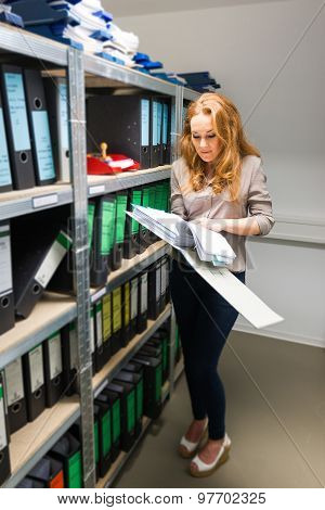 attractive businesswoman searching file in company archives