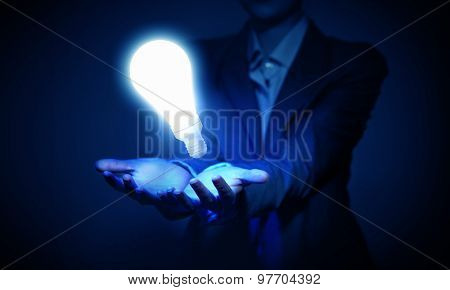 Human hand presenting light bulb concept on palm