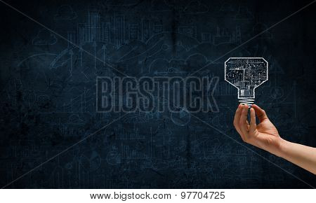Human hand on dark background holding light bulb