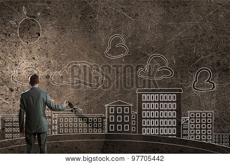 Back view of businessman drawing sketches of construction project on wall