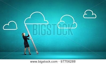 Businesswoman  drawing cloud in sky with huge pencil