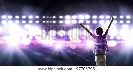 Back view of girl standing in stage lights