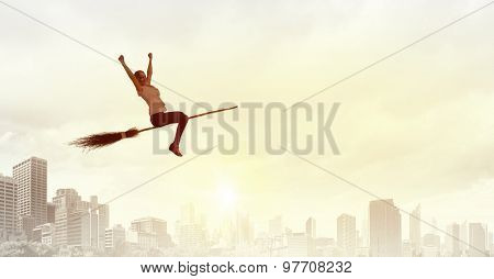 Young girl in casual flying on broom high in sky