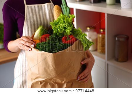 Assorted fruits and vegetables in brown grocery bag holding a young girl