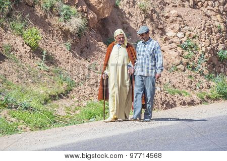 BOUMALNE, MOROCCO, APRIL 11, 2015: Two local men, one in traditional attire, walk on tar road
