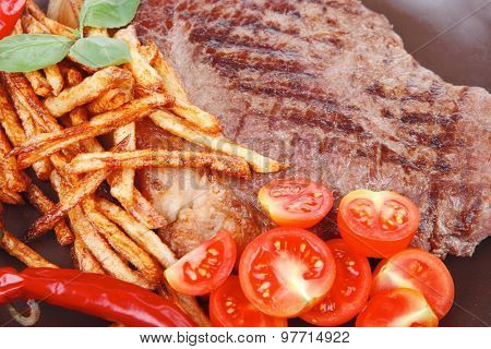 meat food : big grill beef steak on dark plate with red hot chili pepper and raw cherry tomato isolated on white background