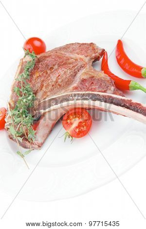 meat food : roast rib on white dish with thyme twig , pepper and tomato isolated over white background