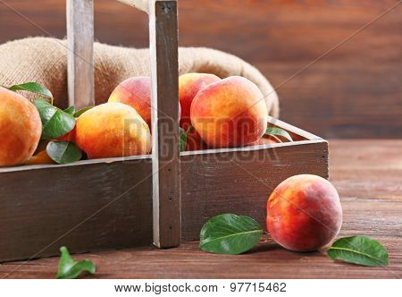 Fresh peaches in crate with sackcloth on wooden table, closeup