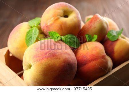 Fresh peaches in wooden crate, closeup
