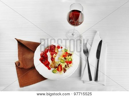 Dish of baked chicken leg and vegetable salad in white plate with glass of wine on table with napkin, closeup