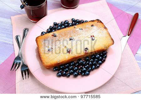 Freshly baked cake with black currants in pink plate on wooden table, top view