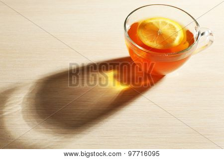 Glass cup of tea with piece of lemon on wooden table background