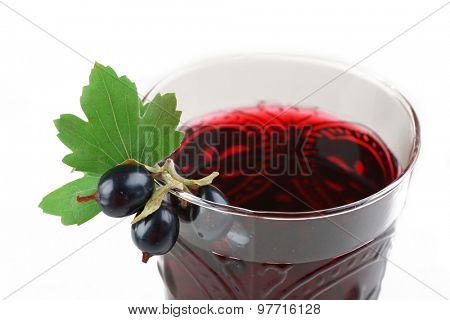 Glass of fresh blackcurrant juice with green leaf on light background