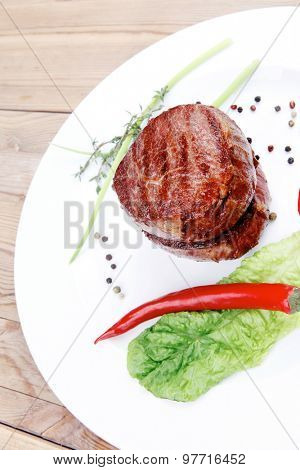 grilled beef fillet medallions with thyme and red hot chili pepper on white plate over wood table