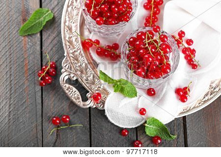 Fresh red currants in glasses on table close up