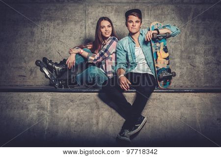 Young couple with skateboard  and rollerblades outdoors