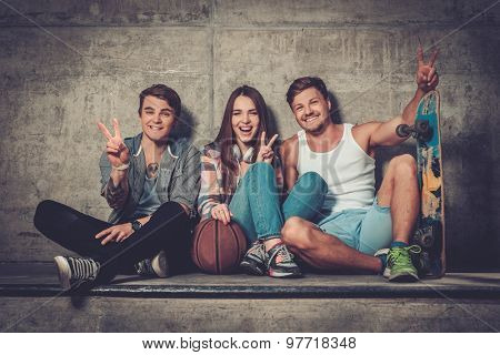 Cheerful friends with with skateboard and ball outdoors