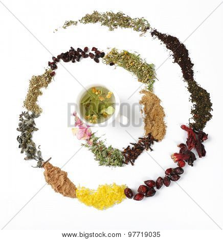 Cup of herbal tea with various kinds of dried herbs isolated on white