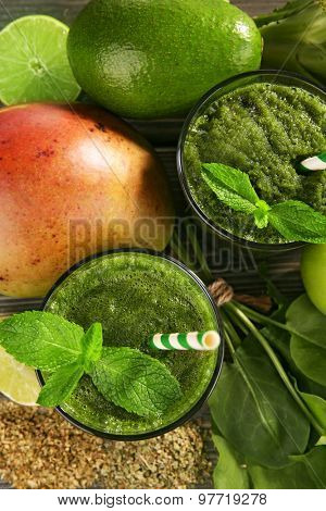 Green healthy juice with fruits and herbs close up