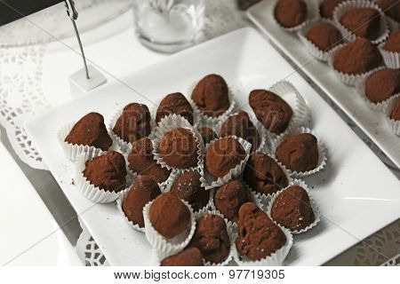 Delicious chocolate candies on plate close up