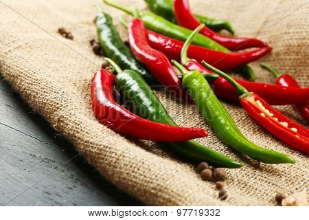 Hot peppers with spices on table close up