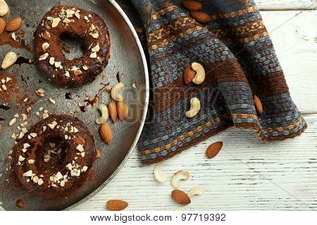 Delicious doughnuts with chocolate icing and nuts on table close up
