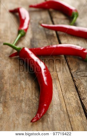 Red hot peppers on wooden table close up