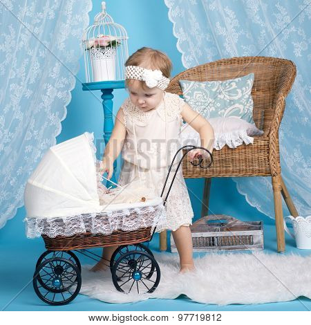 little girl playing with dolls and stroller