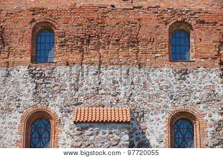 Exterior of the Trakai castle old brick wall with four windows in Trakai, Lithuania.
