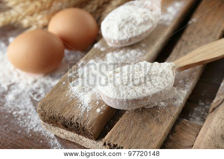 Whole flour with wheat and eggs on wooden table, closeup