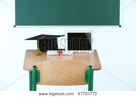 School desk with tablet, master hat and diploma in classroom