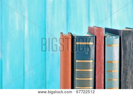 Retro books on turquoise wooden background